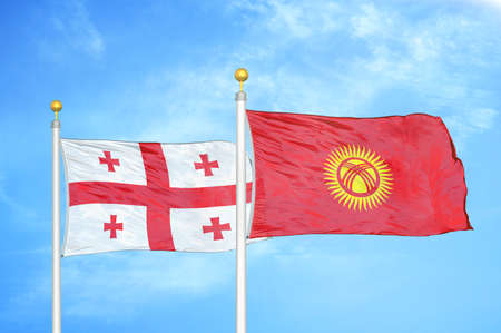 Georgia and Kyrgyzstan two flags on flagpoles and blue cloudy sky background