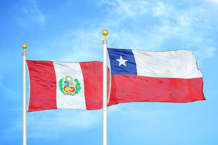 Peru and Chile two flags on flagpoles and blue cloudy sky background
