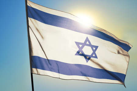 Israel flag waving on the wind in front of sun