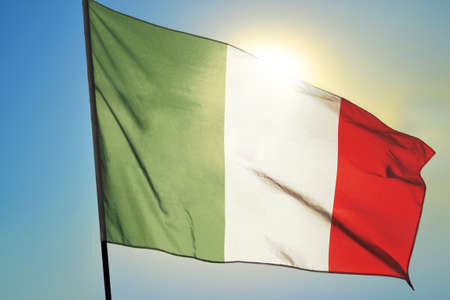 Italy flag waving on the wind in front of sun