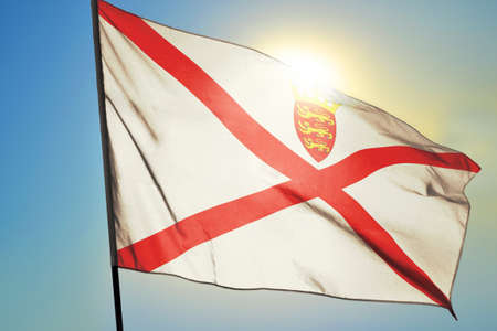 Jersey flag waving on the wind in front of sun
