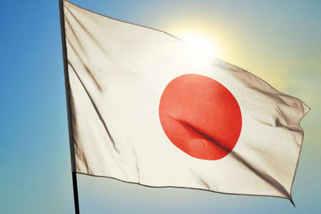 Japan flag waving on the wind in front of sun