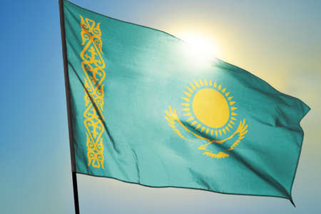Kazakhstan flag waving on the wind in front of sun