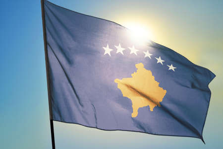 Kosovo flag waving on the wind in front of sun