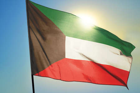 Kuwait flag waving on the wind in front of sun 免版税图像