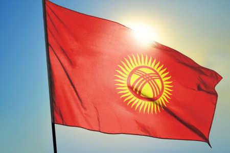 Kyrgyzstan flag waving on the wind in front of sun