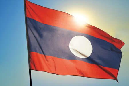 Laos flag waving on the wind in front of sun 免版税图像