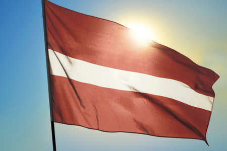 Latvia flag waving on the wind in front of sun