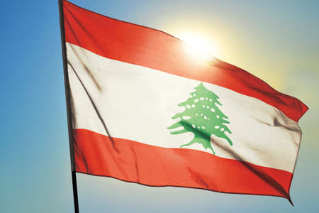 Lebanon flag waving on the wind in front of sun