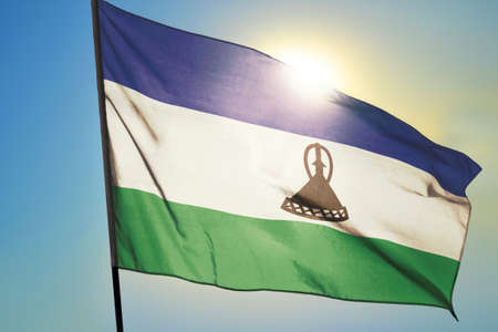 Lesotho flag waving on the wind in front of sun