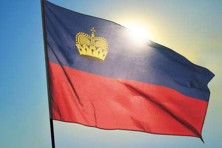 Liechtenstein flag waving on the wind in front of sun