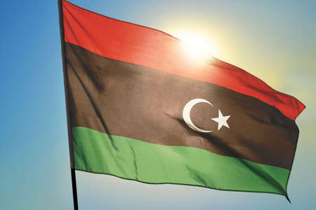 Libya flag waving on the wind in front of sun