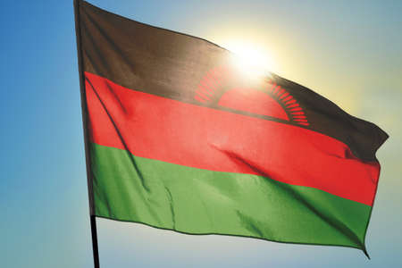 Malawi flag waving on the wind in front of sun 免版税图像