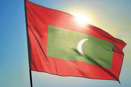 Maldives flag waving on the wind in front of sun