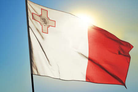 Malta flag waving on the wind in front of sun