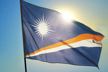 Marshall Islands flag waving on the wind in front of sun