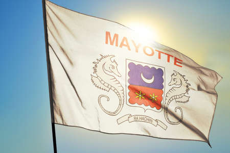 Mayotte flag waving on the wind in front of sun