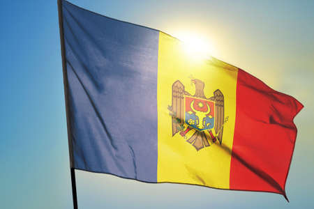 Moldova flag waving on the wind in front of sun Banco de Imagens