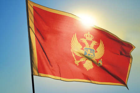 Montenegro flag waving on the wind in front of sun