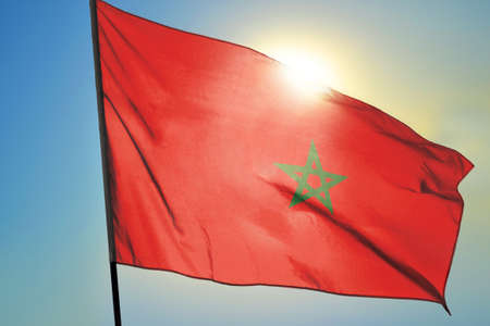 Morocco flag waving on the wind in front of sun