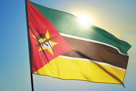Mozambique flag waving on the wind in front of sun 免版税图像