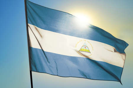Nicaragua flag waving on the wind in front of sun
