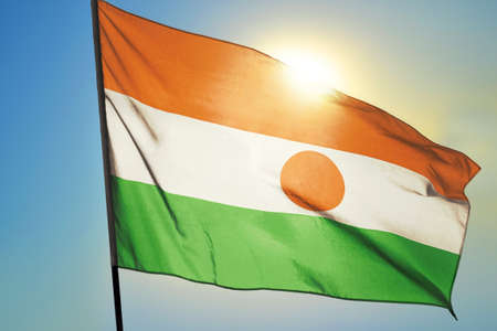 Niger flag waving on the wind in front of sun