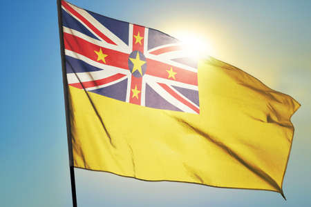 Niue flag waving on the wind in front of sun
