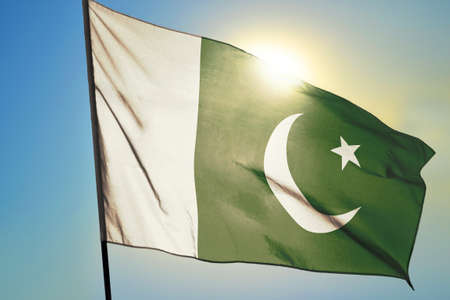 Pakistan flag waving on the wind in front of sun