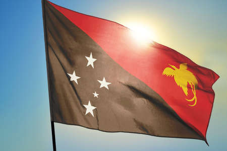 Papua New Guinea flag waving on the wind in front of sun