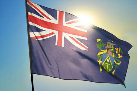 Pitcairn Islands flag waving on the wind in front of sun