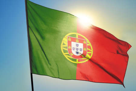 Portugal flag waving on the wind in front of sun