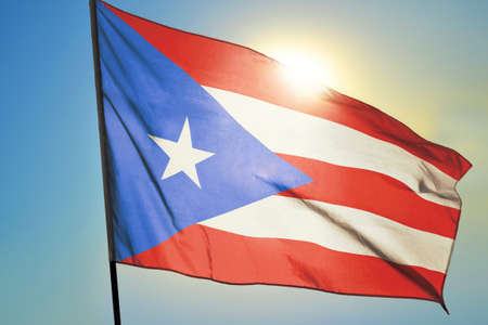 Puerto Rico flag waving on the wind in front of sun 免版税图像