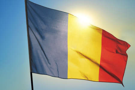 Romania flag waving on the wind in front of sun
