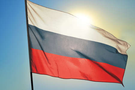 Russia flag waving on the wind in front of sun 免版税图像
