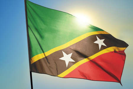 Saint Kitts and Nevis flag waving on the wind in front of sun