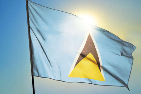 Saint Lucia flag waving on the wind in front of sun
