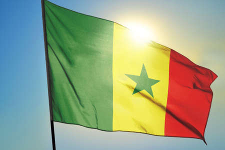 Senegal flag waving on the wind in front of sun