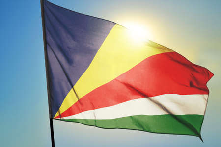 Seychelles flag waving on the wind in front of sun