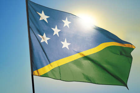 Solomon Islands flag waving on the wind in front of sun