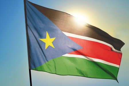 South Sudan flag waving on the wind in front of sun