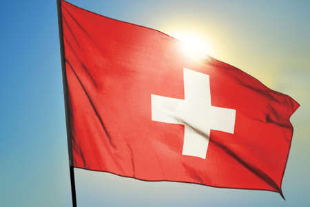 Switzerland flag waving on the wind in front of sun