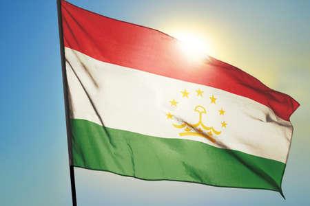 Tajikistan flag waving on the wind in front of sun