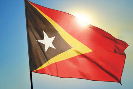 East Timor flag waving on the wind in front of sun