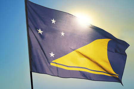 Tokelau flag waving on the wind in front of sun