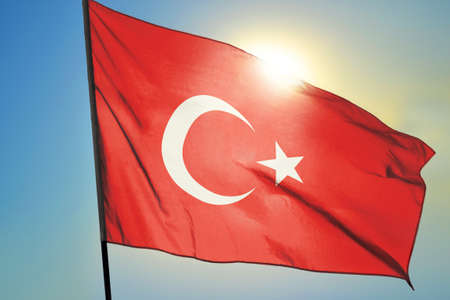 Turkey flag waving on the wind in front of sun