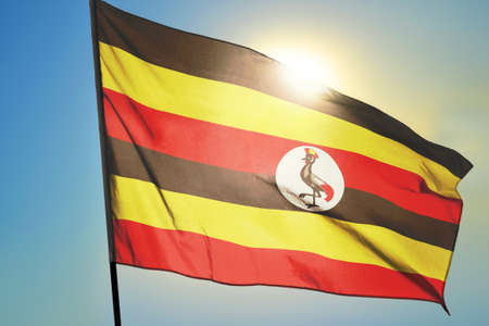 Uganda flag waving on the wind in front of sun