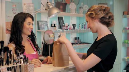 Vue de profil d'une jolie jeune femme de payer par carte de crédit dans un magasin Banque d'images - 69968299