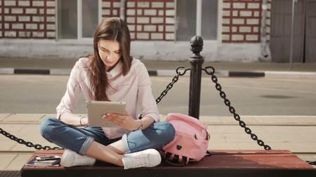 Jeune étudiant en utilisant un ordinateur tablette extérieur d'un bâtiment Banque d'images - 70499235