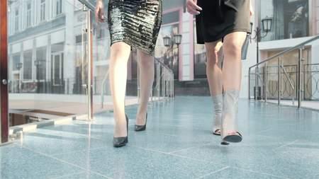Two friend women walking cross legged wearing heels in shopping mall